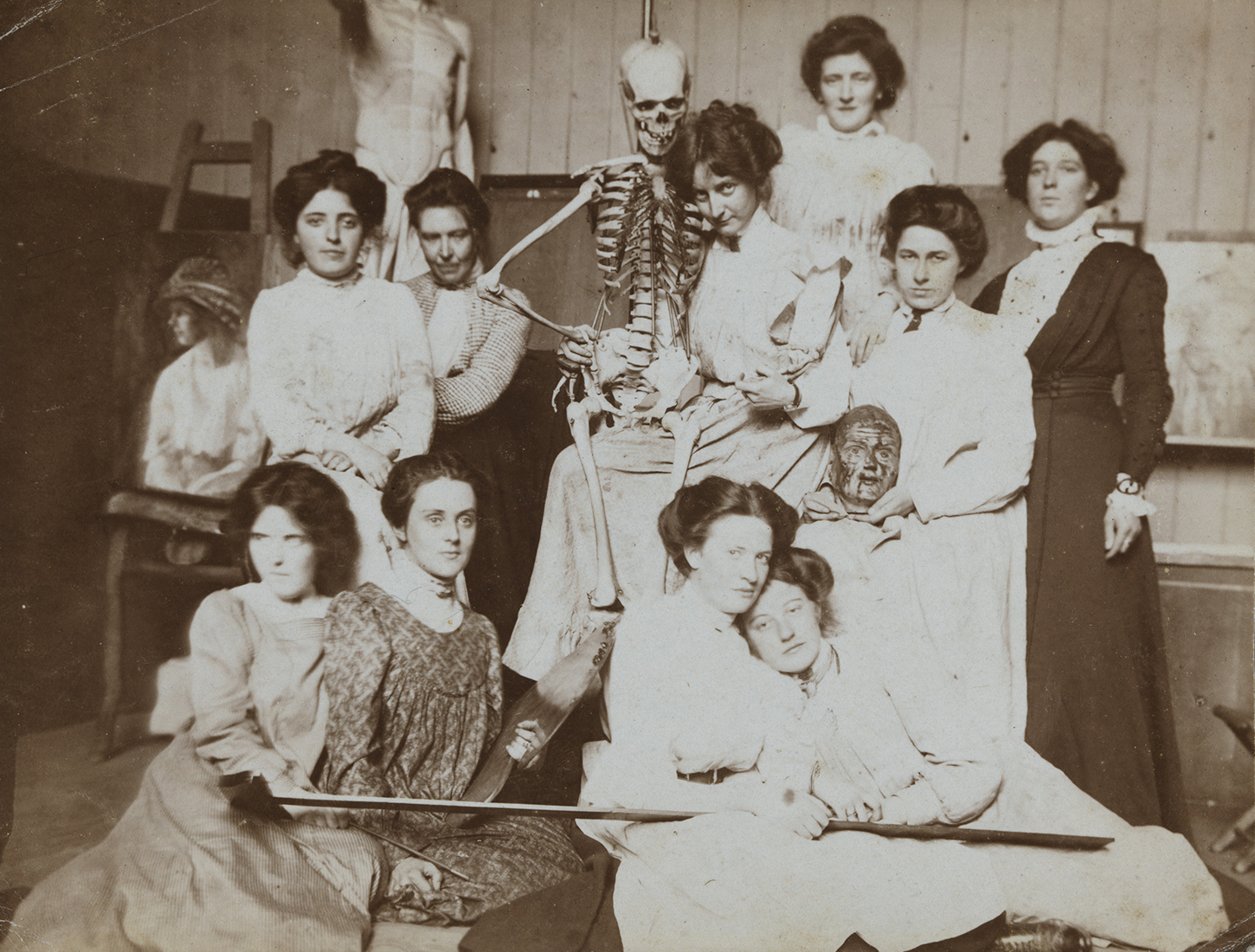 Vintage black and white photo of women posing with a medical skeleton model