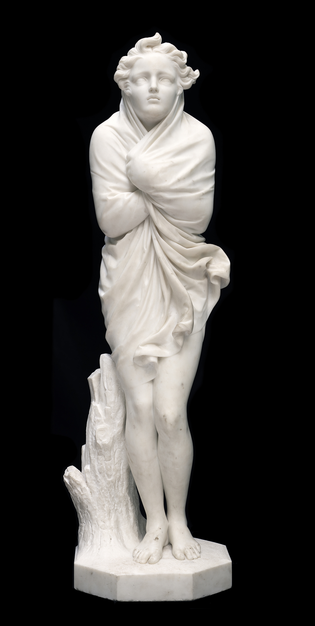 A marble sculpture of a female figure, wrapping a shawl tightly around herself against the cold