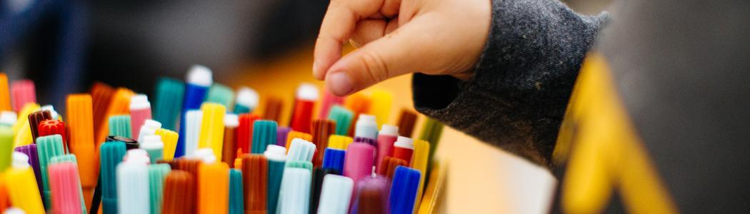 Photo of a child's hand picking a felt tip pen out of a box.