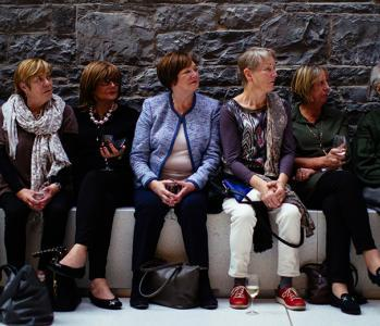 Photo of six women and a man seated in a row on a bench against a stone wall.