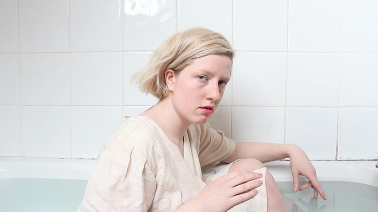 Still image from a video showing a young woman wearing white and seated in a bath full of water.