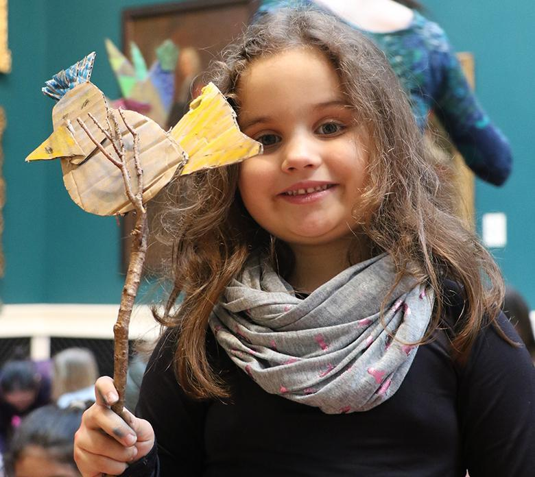 A child holding up her artwork created at a drop-in family workshop in the National Gallery of Ireland.