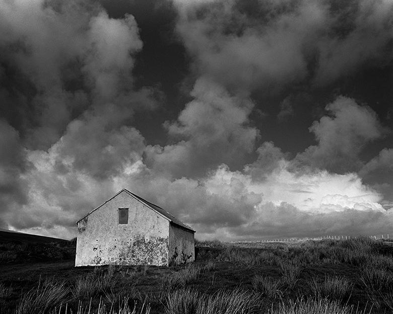 A black and white photograph with a low horizon and expansive cloudy sky, with simple whitewashed cottage standing in a field.
