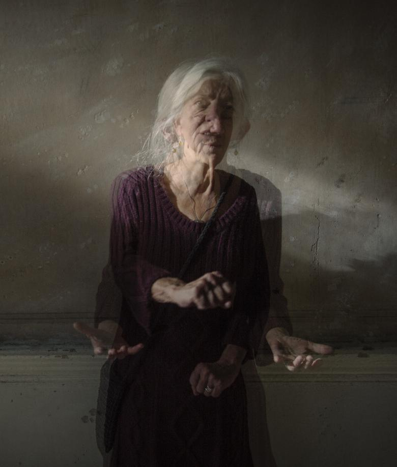 This portrait has the effect of a moving image within a still image. The subject is sitting in a shaft of light in a dimly lit background. She appears very animated, with her hands and head in motion.