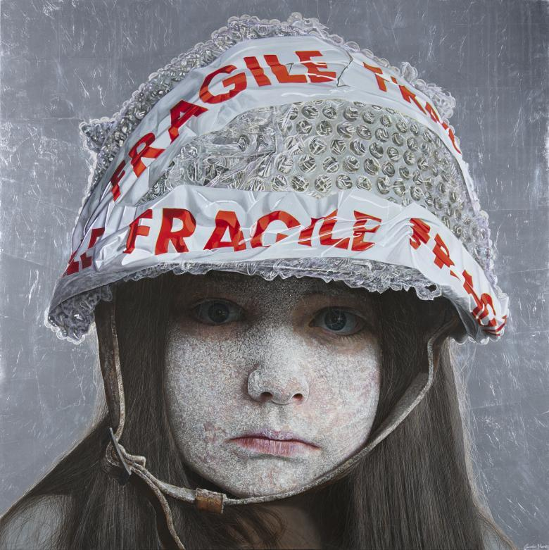 A child stares directly at the viewer. Her face is coated in a white dust-like substance, and she wears a helmet on her head, fastened under her chin. The helmet is covered in bubble wrap, and has red and white tape on it with the word 'Fragile'.