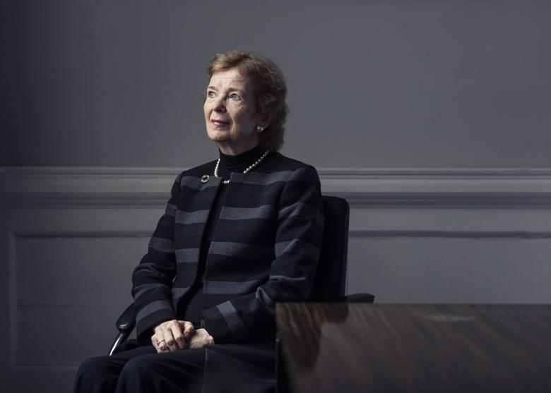 Former President of Ireland Mar Robinson sits beside a wooden table with her hands clasped in her lap. She is dressed in a grey and black striped jacket with a brooch at the lapel, and she gazes upwards and to her right.