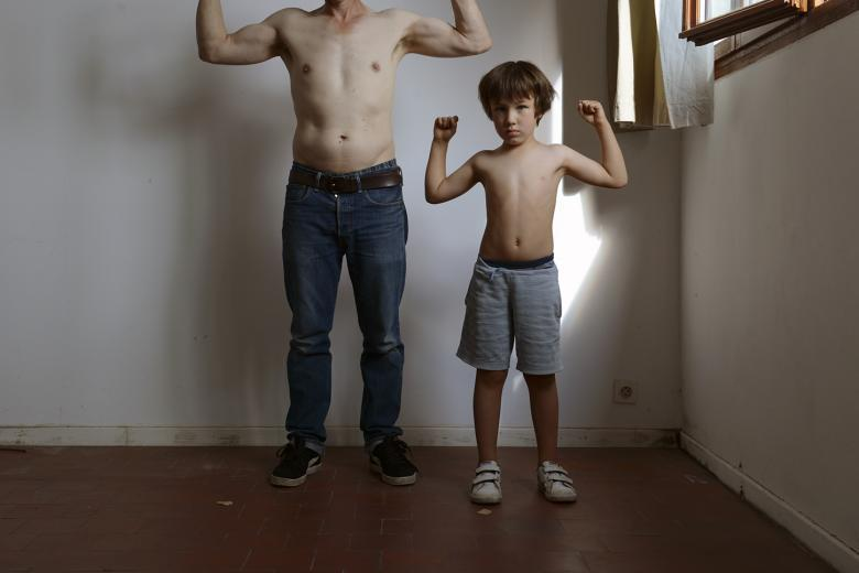 Two figures - an adult and a child - stand in an empty room against a white wall. Both are topless, with the adult figure in jeans and the child in shorts. They both have their arms raised as though holding an imaginary weight over their heads. The adult figures head is not visible, but the child looks directly at the camera, and there is a shaft of light from the open window behind him.