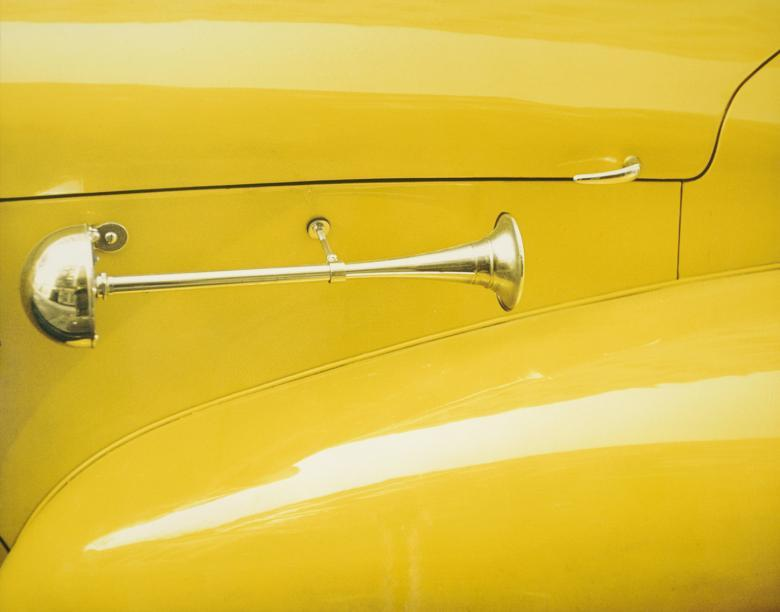 Closely cropped colour photo of a yellow car