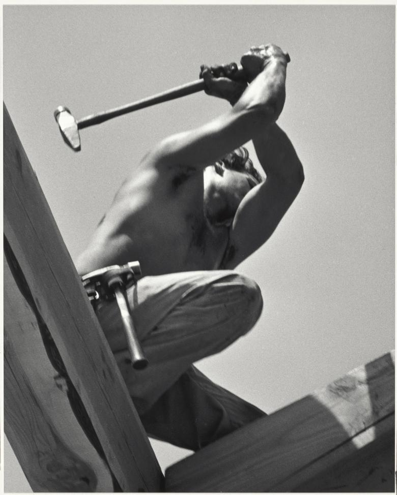 Black and white photo taken from a low angle showing a shirtless man kneeling on wood, with a hammer raised over his head