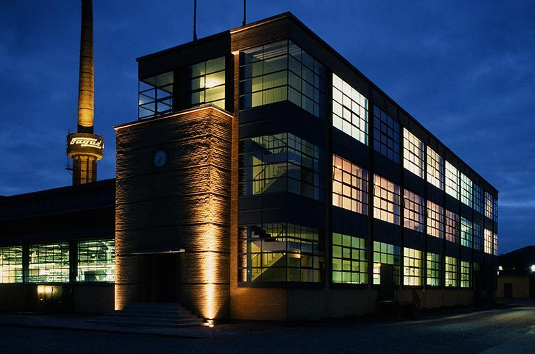 Nighttime photo of a Bauhaus building with lights inside illuminating the windows.
