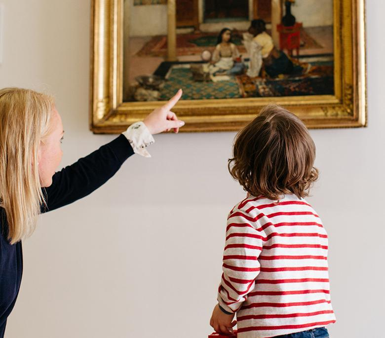 A woman crouched down beside a small child and pointing at a painting on a tour of the National Gallery of Ireland.