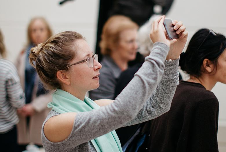 A woman holding up a mobile phone to take a photograph in the Gallery.