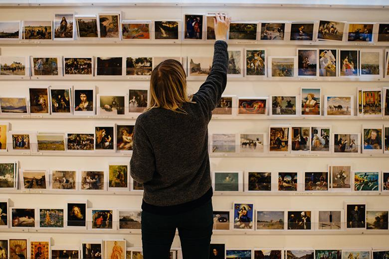Photo of a woman standing, with her back to the camera, in front of a wall displaying postcards.