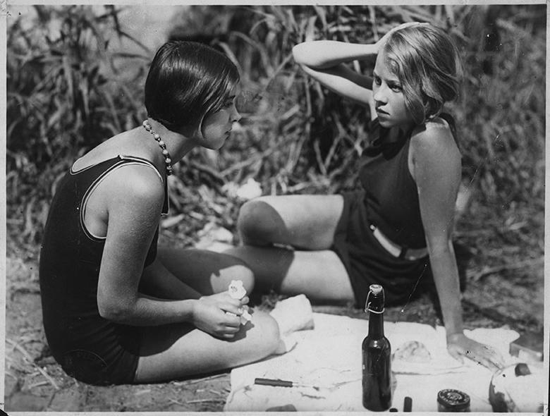 Black and white still from People on Sunday film showing two women in bathing suits having a picnic.
