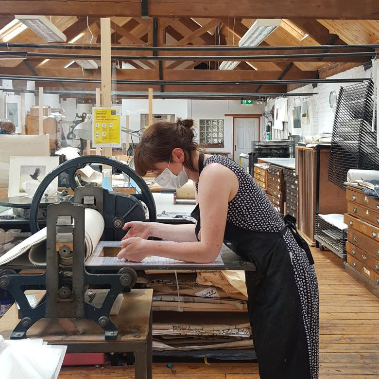 Artist working at a printing press in Graphic Studio Dublin
