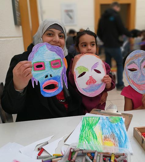 A family hold up the masks that they created at a drop-in family workshop at the National Gallery of Ireland.