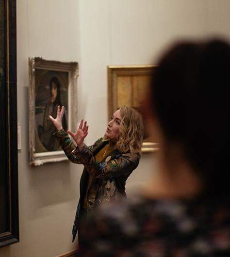 Photo of a tour guide speaking to a group of visitors in front of John Lavery's painting The Artist's Studio, in the National Gallery of Ireland.