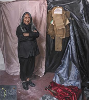 Painted full-length portrait of designer John Rocha wearing all black and standing in front of a wall covered in sheets of fabric and paper patterns.
