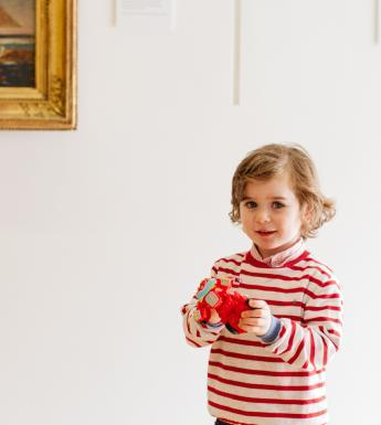 A child standing in front of a gold-framed painting in the Gallery