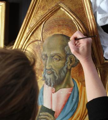 Conservator retouching an altarpiece painting