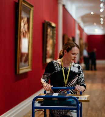 Woman pushing trolley of books through art gallery