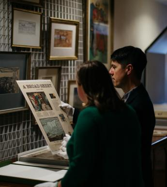 Two people looking at archival material