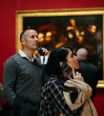 Visitors to Beyond Caravaggio listening to audio guides. © National Gallery of Ireland.
