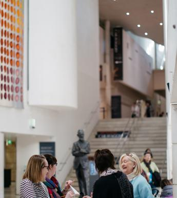 Visitors at the information desk in the Millennium Wing. © National Gallery of Ireland.
