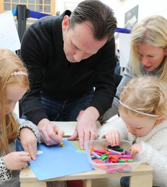 A man, woman and two children working together to create artwork at a drop-in family workshop in the National Gallery of Ireland.