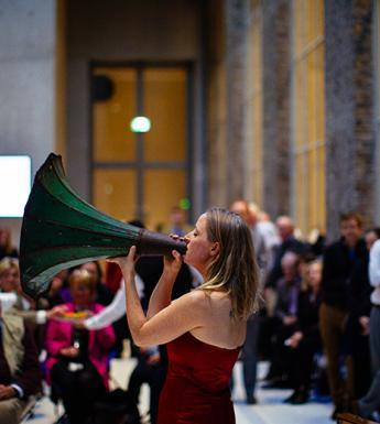 Photo of people attending an event with a woman playing speaking through a gramophone horn.