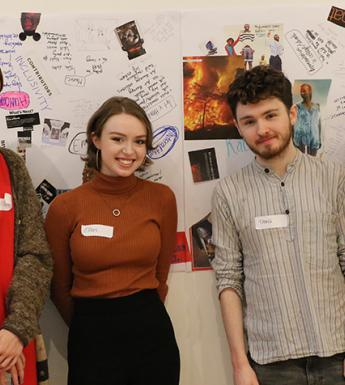 Photo of three young women and one young man posing in front of a collage