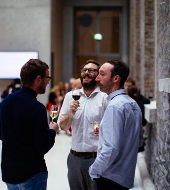 Photo of three men drinking wine at an event in the Courtyard of the National Gallery of Ireland.
