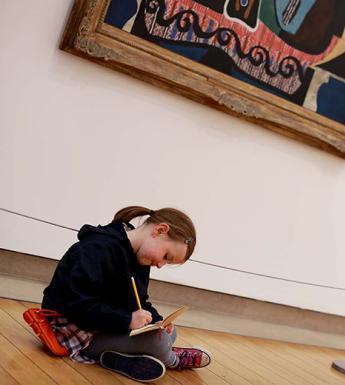 Photo of a young girl sitting on the floor in a gallery and drawing.