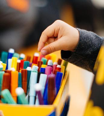 Photo of a child's hand reaching for a coloured marker in a box.