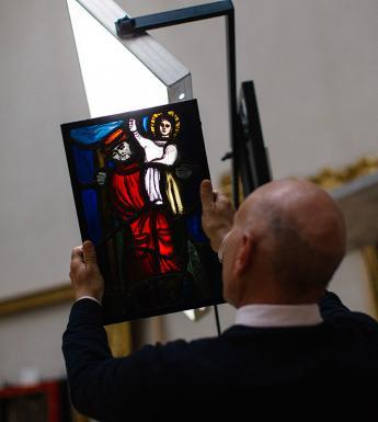 Photo of a man with his back to the camera, holding up a piece of stained glass so that the light shines through it.
