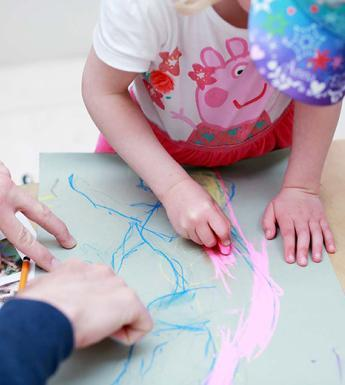 Photo of a young child drawing with an adult's hands stabilising the piece of paper.