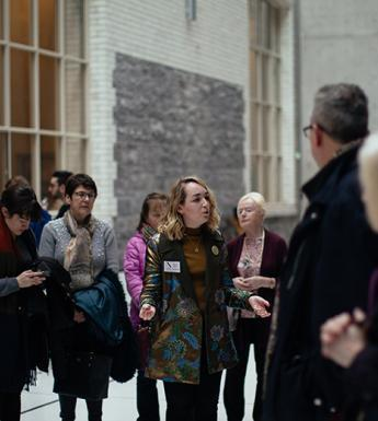 Photo of a tour guide speaking to a group of visitors in the courtyard of the National Gallery of Ireland.
