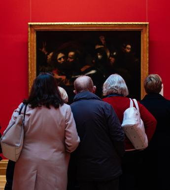 Photo of a group of people, with their backs to the camera, looking at Caravaggio's painting of the Taking of Christ, which is hanging on a red wall.