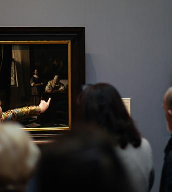 Photo of a tour guide speaking to a group of visitors in front of Vermeer's painting of a woman writing a letter in the National Gallery of Ireland.