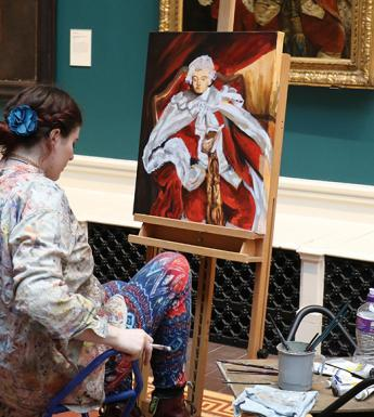 Photo of a young woman, dressed in paint-covered clothes, seated at an easel in a gallery and copying from a portrait.