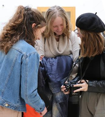 Photo of three young women looking at a digital camera screen