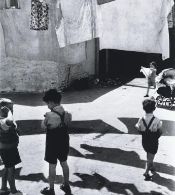 Black and white photograph of children playing in a yard beneath a clothes line of washing.