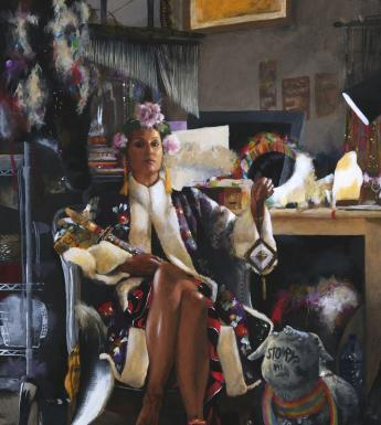 A woman sits in a chair, looking directly at us. She is dressed in a patterned jacket with white fur trim, and wears a floral headdress and tasselled earrings. In her hand she holds aloft a dream catcher.
