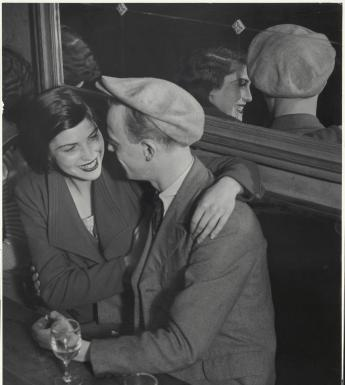 A black and white photograph of a woman and a man sitting side by side at a table, with two half full glasses of wine in front of them. They are turned towards each other, and the woman has her arm around the man's shoulder, and is smiling. Behind them is a large mirror in which we can see them reflected.