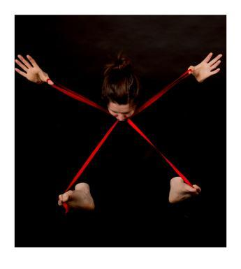 Emerging from a black background we see the head of a woman, eyes cast down, and her hands and feet. There is a red ribbon in the shape of an X connecting the part of her body we see.
