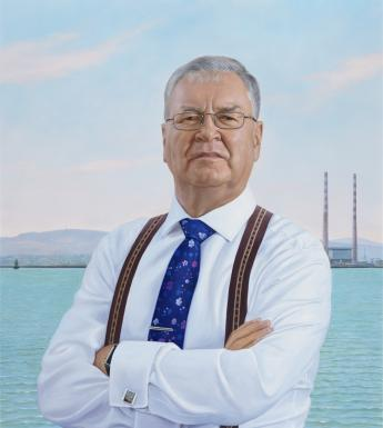 Three quarter length portrait of a man. He is wearing a white shirt, braces, and a blue tie. In the background we can see the sea, the mountains, and the Poolbeg towers.
