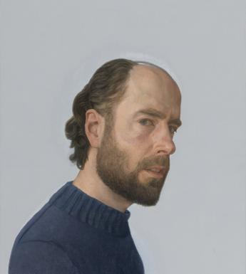 The subject of the portrait is standing side-on to the viewer, but his head is turned to look directly at us. He wears a navy woollen jumper.