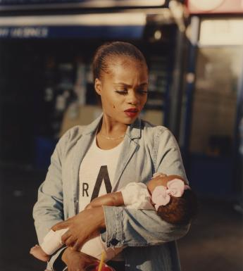 A woman dressed in a denim blazer and white t-shirt gazes down at the infant she cradles in her arms. The infant appears to be asleep, and has a large pink bow on her head. In the hand that is not holding the baby, the woman holds a red iced drink with a straw.