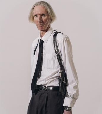 A three quarter length portrait of a male figure dressed in a white shirt, black tie, and back pants. He has white hair, and is looking directly at the viewer. He wears a black holster across his shoulders, which, when we look closely, holds a notebook and pen.