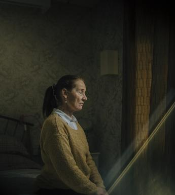 A woman in a mustard-coloured jumper over a white shirt sits on a bed with her eyes closed and her hands in her lap. She is turned towards a curtained window, and a shaft of light is coming into the darkened room in which she sits.